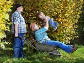 Farmer's family in their orchard. Autumn on countryside.