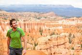 Hiker - man hiking in Bryce Canyon national park. Happy male outdoorsman walking enjoying outdoor activity walking in beautiful nature landscape in Utah, USA.