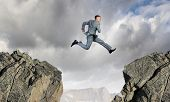 stock photo of interrupter  - Young businessman jumping over mountain gap - JPG