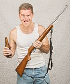 stock photo of hillbilly  - Single male hillbilly holding beer and rifle - JPG