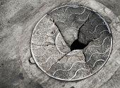 Old Broken Manhole Cover On The Asphalt Road