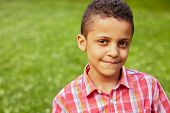 stock photo of mulatto  - Closeup portrait of mulatto boy in red checkered shirt - JPG