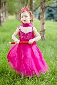 Little girl dressed in bright puffy gown  stands on grassy lawn in park holding big red pencil in he