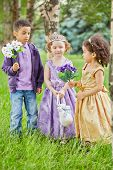 Boy and two little girls dressed in party frocks stand in park on grassy lawn, boy and one of girl h