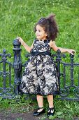 Little girl in black gown stands leaning on black wrought-iron fence
