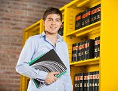 Portrait of confident male student holding books standing by shelf in university library