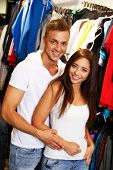 Beautiful young couple choosing sportswear in sport outlet