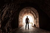 stock photo of tunnel  - Young man stands in dark concrete tunnel and looks out in the glowing end - JPG