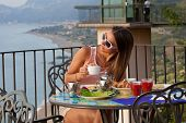 Young Woman Having Breakfast At Resort Restaurant Outdoor