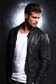 stock photo of hunk  - side view of a serious young fashion model in leather jacket looking away from the camera - JPG