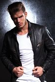 young fashion model in leather jacket posing for the camera