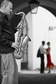 Black and white photograph street musician playing his saxophone while a romantic couple can be seen out of focus in the background the woman is in color wearing a red dress