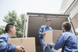 image of moving van  - Movers unloading a moving van and passing a cardboard box - JPG