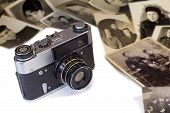 stock photo of outdated  - The outdated film camera and ancient black white photos on a white background - JPG