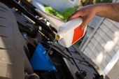 stock photo of lube  - A backyard mechanic pours motor oil into the engine at the end of an oil change - JPG