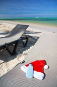 Santa Hat And Sun Tan On Chaise Longue