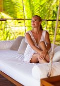 Beautiful girl sitting on swing in the beach house on Maldives, relaxation outdoors, luxury summer holidays in paradise