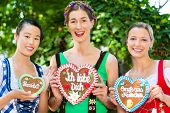 Young women in traditional Bavarian clothes or tracht with a gingerbread souvenir heart in beergarde