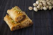 image of baklava  - Baklava with Pistachio Nuts on a Black Mat