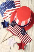 High angle shot of assorted items to celebrate the Fourth of July. Items include, Uncle Sam Hat, American Flags, napkins and red white and blue decorative stars. Vertical format with a vintage look.