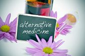 foto of naturopathy  - a dropper bottle and some flowers with a blackboard label with the text alternative medicine written on it - JPG