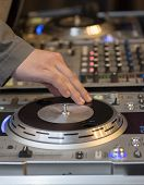 stock photo of disc jockey  - Hand of a DJ rotating his equipment to produce effects - JPG