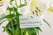 foto of sweethearts  - Happy anniversary floral gift of a bouquet of fresh white lilies with a hand - JPG