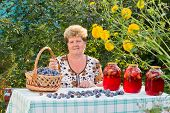 elderly woman with a jar of plum compote