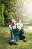 stock photo of dungarees  - Gardener in dungarees sitting on the grass