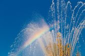 stock photo of refraction  - refraction of light in the spray of the fountain and colored rainbow appeared on the background of blue sky - JPG
