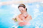 Young Mother And Her Newborn Baby Son Having Fun In A Swimming Pool