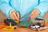Master checks electronic hardware with a multimeter in service workshop
