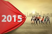 picture of metaphor  - Young business people try to pull number 2015 symbolizing an effort for progress in 2015 - JPG