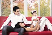 Joyful Hispanic Family On Sofa