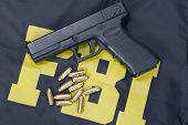 stock photo of ammo  - 9mm handgun with ammo on FBI uniform - JPG