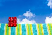Three Red Plastic Clothespins And Multicolor Cotton With The Blurry Blue Sky Background.