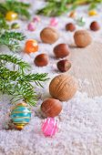 pic of hazelnut tree  - Walnuts and hazelnuts lie on the surface of wood against the white snow surrounded by fir branches and bright balls