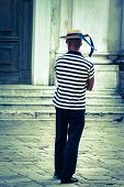 stock photo of gondolier  - Gondolier on the docks awaiting tourists in Venice Italy Europe - JPG