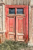 Aged red door with two glass windows on the top in old slum house in Astrakhan, Russia