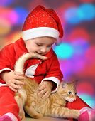 Happy Small Girl In Santa Red Hat Playing With Kitten