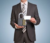 picture of combination lock  - Businessman in suit hold empty card and combination lock - JPG