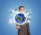 Businessman hold Earth with electronics, graphs and network