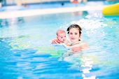 Young Beautiful Mother And Her Newborn Baby Enjoying Swimming In A Pool