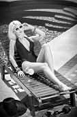 Beautiful sensual blonde with fashionable sun glasses relaxing at swimming pool with a juice