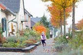 Cute Toddler Girl Running On A Beautiful Street In A Small European Village In Autumn