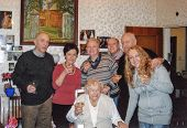 Vintage photo of elderly woman raising her glass with her family, nineties