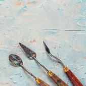 Three Old Palette Knifes On Artist Canvas With Coating Of Oil Paint