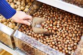 Hazelnut On Store Shelves And Buyer's Hand With Shovel