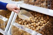 Walnuts On Store Shelves And Hand Buyer With Shovel
