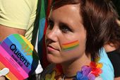 PRAGUE, CZECH REPUBLIC - AUGUST 17, 2013: Young woman with rainbow flags drawn on her face attends the Prague Gay Pride Festival in Prague, Czech Republic.